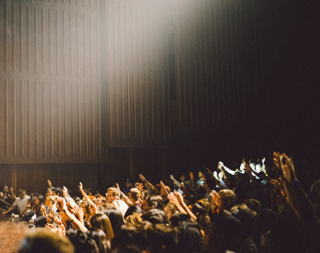 Picture of an audience in a lecture theatre, many people with raised hands. Photo by Edwin Andrade on Unsplash.